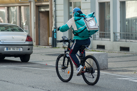 Mulhouse - France - 6 January 2019 - Delivery man with bicycle in the street,  deliveroo is a british delivery company  in mountain bike Reklamní fotografie - 114643580