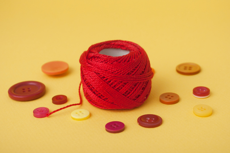 closeup of red string bobbin and plastic buttons on yellow background
