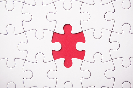 the last piece of jigsaw puzzle missing on red background to complete the mission Standard-Bild - 116234458