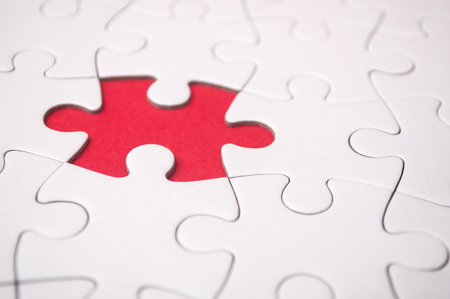 the last piece of jigsaw puzzle missing on red background to complete the mission Standard-Bild - 116234469