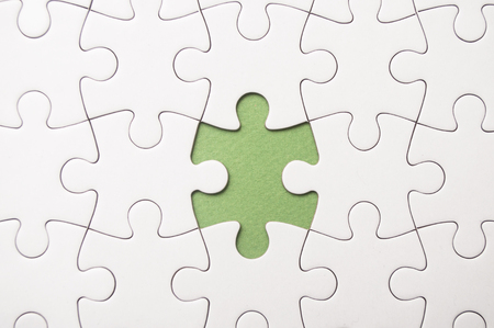 the last piece of jigsaw puzzle missing on green background to complete the mission Standard-Bild - 116234471