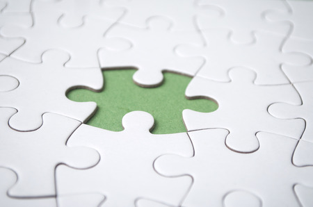 the last piece of jigsaw puzzle missing on green background to complete the mission Standard-Bild - 116234481