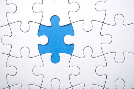 closeup of the last piece of jigsaw puzzle missing on blue background to complete the mission Standard-Bild - 116234501