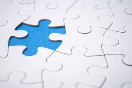 closeup of the last piece of jigsaw puzzle missing on blue background to complete the mission Standard-Bild - 116234524