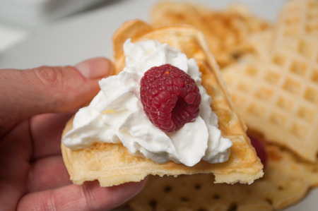 closeup of waffle in shaped heart with  chantilly cream and raspberry in hand