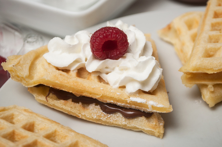 closeup of waffle in shaped heart with chantilly cream and raspberry in a white plate