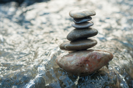 Closeup of stone balance on rock in the river