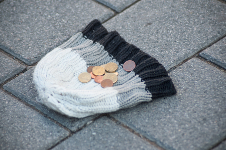 closeup of euro coins on wool hat in the street - concept poverty