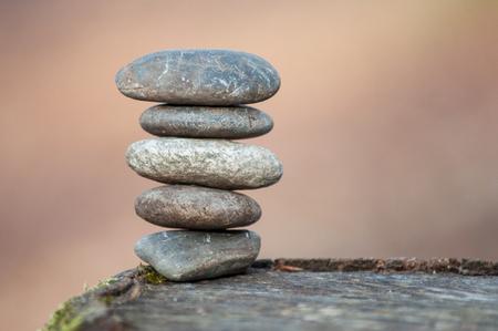 Primer plano de equilibrio de piedra en el tocón de un árbol en el bosque