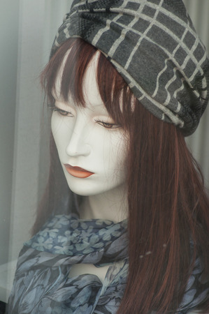 closeup of wig and scarf on mannequin in fashion store showroom