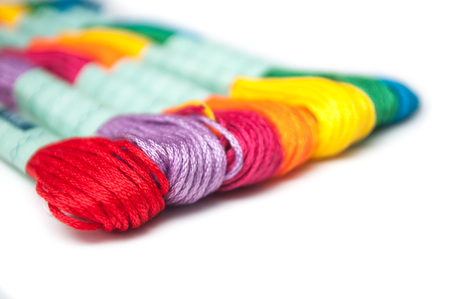 closeup of colorful cotton threads on white background