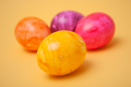 closeup of decorative painted easter eggs on yellow background