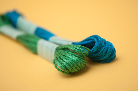 closeup of colorful cotton threads on yellow background
