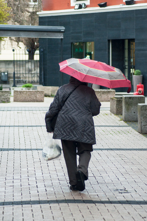 Mulhouse - France - 3 April 2019 -  portrait of old woman with pink umbrella and grey coat in the street on back view Editorial