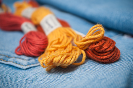 closeup of colorful cotton threads on blue jeans background