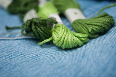 closeup of green cotton threads on blue jeans background