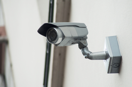 closeup of grey security camera on stoned wall background