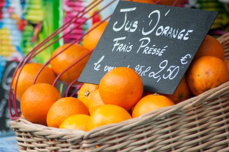 "Closeup of organic oranges in a wooden basket at the market with text in french on chalkboard ""Jus d'orange frais pressé"", traduction in english : fresh orange juice"