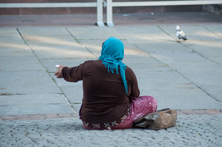 Strasbourg - France - 20 April 2019 -  poor woman  with plastic cup in hands sitting in the street