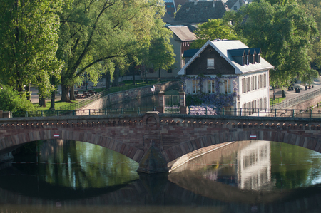 panorama of stoned bridge in little France quarter in Strasbourg with reflection