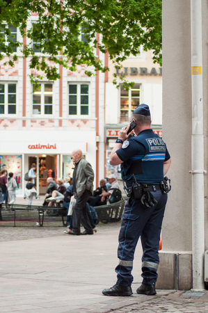 Mulhouse - France - 25 April 2019  - Portrait of french municipal policeman standing on main place with telephone in hand