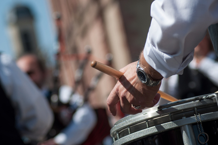 closeup of hand of drummer in scottish band playing in the street
