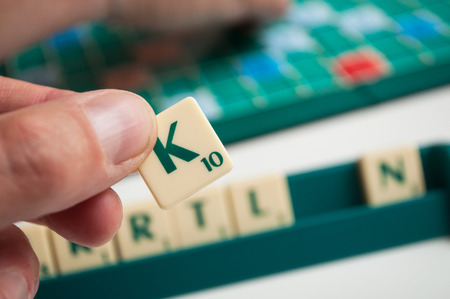 Mulhouse - France - 4 May 2019  - Closeup of plastic letters K in hand on Scrabble board game Standard-Bild - 122444742