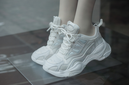 Closeup of white sneakers on mannequin in fashion store showroom for women