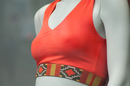 closeup of orange sport bra on mannequin in fashion store showroom for women
