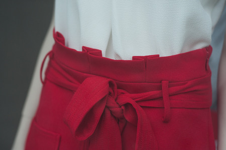 closeup of ribbon belt on red skirt on mannequin in fashion store showromm for women