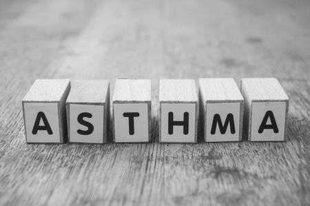 Closeup of word on wooden cube on wooden desk background concept - Asthma