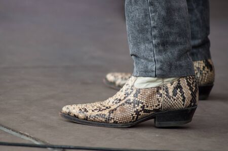 closeup of man feet with snake american boots at country show in outdoor
