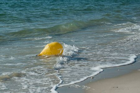 closeup of yellow buoy in the water oin the beach