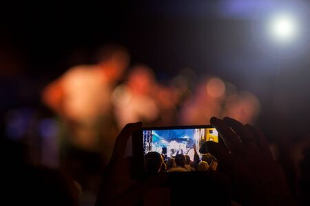 Closeup of people with smartphone in hands taking a photo in a concert