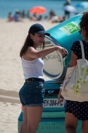 Quiberon - France - 12 July 2019 - Portrait of sexy girls with jeans short and white teeshirt giving fresh red bull cans on the beach Editorial