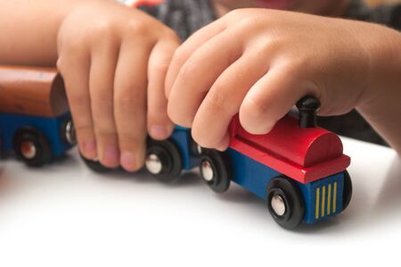 Closeup of hand of kid playing with wooden train on white background