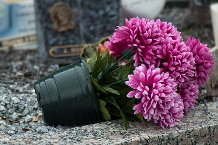 closeup of artificial flowers on tomb in cemetery