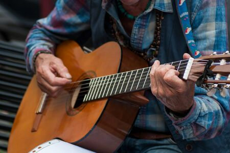 closeup of hands of old man playing on acoustic guitar in the street