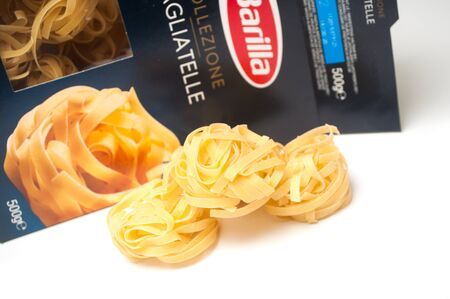 Mulhouse - France - 21 August 2019 - Closeup of tagliatelle pasta falling from Barilla cardboard box on white background, the famous brand of italian pasta