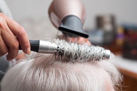 Closeup of hands of hairdresser on old woman with gray hairs - hairdresser at home concept