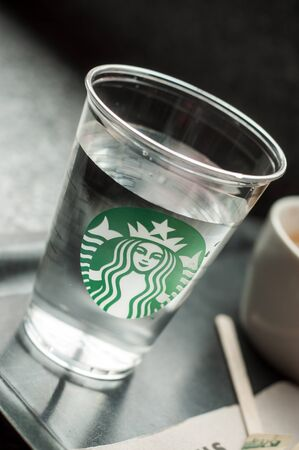 Mulhouse - France - 8 September 2019 - Closeup of Starbucks logo on a transparent glass on a Starbucks coffee table