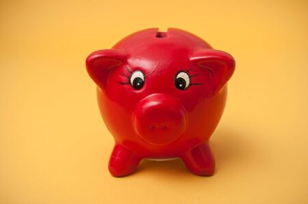 Closeup of red piggy bank on yellow background Banco de Imagens