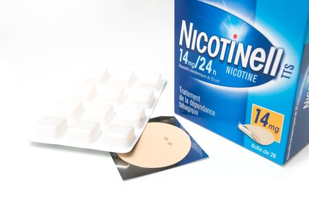 Mulhouse - France - 18 September 2019 - Closeup of nicotinelle patch and nicotine candy on white background