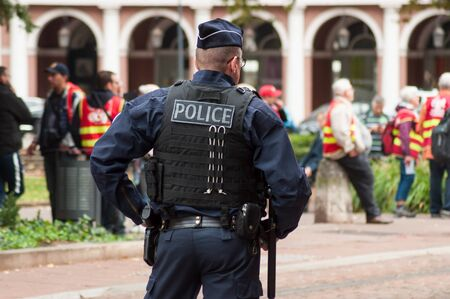 Mulhouse - France - 24 September 2019 - portrait on back view of policeman standing in the street during the protest against pension reform