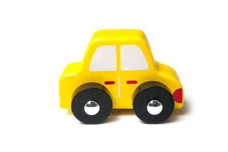 closeup of yellow miniature wooden car on white background 写真素材