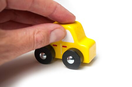 closeup of miniature wooden car in hand on white background