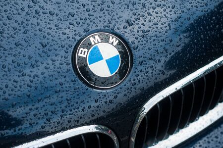 Mulhouse - France - 10 October 2019 - Closeup of rain drops on blue BMW car front parked in the street