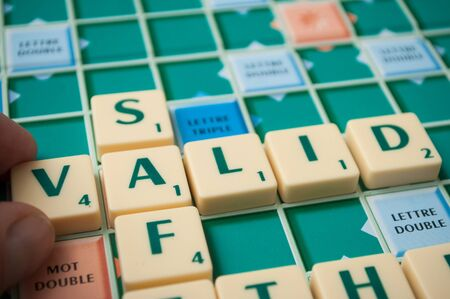 Mulhouse - France - 11 October 2019 - Closeup of plastic letters on Scrabble board game forming the word : Valid Foto de archivo - 131404307