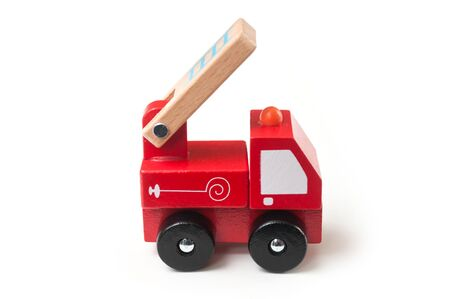 Closeup of miniature toy, wooden fire truck on white background Stock Photo