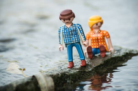 Mulhouse - France - 12 October 2019 - Closeup of PLaymobil characters on rock in middle of the river in outdoor